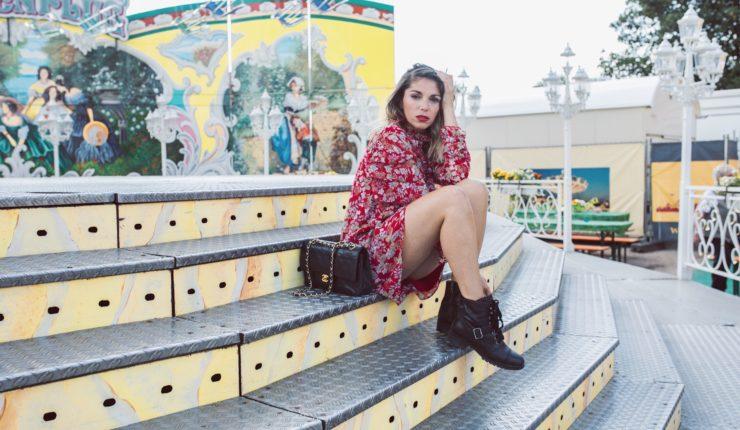 rotes kleid vor karussell sitzend